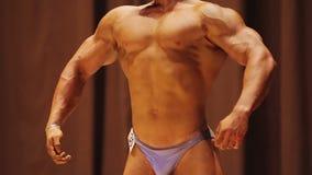 Οι αθλητικοί μυ'ες επίδειξης ατόμων, μπροστινό lat που διαδίδεται θέτουν, bodybuilding ο διαγωνισμός φιλμ μικρού μήκους