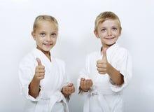 Οι αθλητές παιδιών με τις ζώνες παρουσιάζουν αντίχειρα έξοχο Στοκ φωτογραφία με δικαίωμα ελεύθερης χρήσης