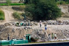 Οι αιγυπτιακοί εργαζόμενοι φορτώνουν τις πέτρες με το χέρι σε μια φορτηγίδα στον ποταμό του Νείλου στοκ εικόνες