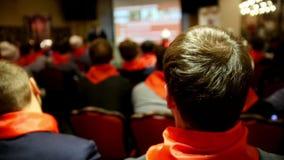Οι ακροατές στους κόκκινους δεσμούς αφουγκράζονται τον ομιλητή που λέει και παρουσιάζει παρουσίαση για την οθόνη φιλμ μικρού μήκους
