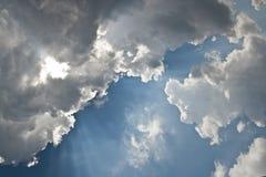 Οι ακτίνες λάμπουν μέσω των σύννεφων Στοκ Εικόνες