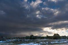 Οι ακτίνες ήλιων κάνουν τον τρόπο τους μέσω του σκοτεινού δραματικού ουρανού Στοκ Εικόνα