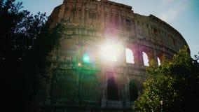 Οι ακτίνες ήλιων ` s λάμπουν μέσω των αψίδων του διάσημου Colosseum στη Ρώμη steadicam πυροβολισμός φιλμ μικρού μήκους