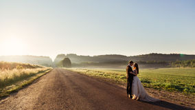 Οι ακτίνες του φωτός βραδιού καλύπτουν το δρόμο όπου το γαμήλιο ζεύγος στέκεται Στοκ φωτογραφία με δικαίωμα ελεύθερης χρήσης