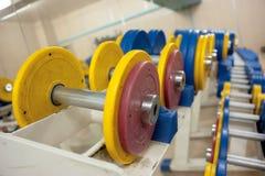 Οι αλτήρες με τους κίτρινους και κόκκινους δίσκους φορτίου στη γυμναστική βρίσκονται σε μια σειρά Υπόβαθρο Στοκ Φωτογραφίες
