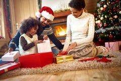 Οι αμερικανικοί γονείς Afro με την κόρη ανοίγουν τα χριστουγεννιάτικα δώρα Στοκ εικόνες με δικαίωμα ελεύθερης χρήσης
