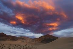 Οι αμμόλοφοι άμμου και ένα φλογερό ηλιοβασίλεμα δημιουργούν ένα δραματικό τοπίο στοκ φωτογραφία με δικαίωμα ελεύθερης χρήσης