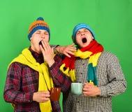 Οι αμφιθαλείς πίνουν την καυτή σοκολάτα και το χασμουρητό Δίδυμα με τα κουρασμένα πρόσωπα Στοκ Εικόνες