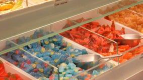 Οι ανάμεικτες ζωηρόχρωμες καραμέλες ζελατίνας στο μετρητή σε ένα κατάστημα αγοράς τροφίμων, γερμανικά ονόματα καραμελών, ζύγισμα  απόθεμα βίντεο