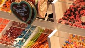Οι ανάμεικτες ζωηρόχρωμες καραμέλες ζελατίνας στο μετρητή σε ένα κατάστημα αγοράς τροφίμων, γερμανικά ονόματα καραμελών, ζύγισμα  φιλμ μικρού μήκους