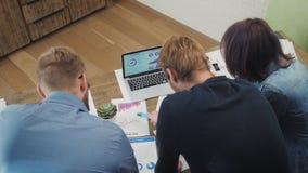 Οι αναλυτές στο γραφείο εργάζονται στο lap-top που παρουσιάζει στατιστικές, εξετάζοντας τις γραφικές παραστάσεις και τα διαγράμμα φιλμ μικρού μήκους
