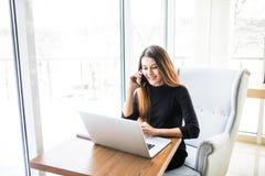 Οι ανεξάρτητες νεολαίες χαμογελούν τη συνεδρίαση γυναικών στην καφετέρια με το lap-top και τη χρησιμοποίηση του κινητού τηλεφώνου Στοκ φωτογραφία με δικαίωμα ελεύθερης χρήσης