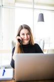 Οι ανεξάρτητες νεολαίες χαμογελούν τη συνεδρίαση γυναικών στην καφετέρια με το lap-top και τη χρησιμοποίηση του κινητού τηλεφώνου Στοκ φωτογραφίες με δικαίωμα ελεύθερης χρήσης