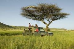 Οι ανιχνεύσεις και ο τουρίστας Masai ψάχνουν τα ζώα από ένα Landcruiser κατά τη διάρκεια μιας κίνησης παιχνιδιών στη συντήρηση άγ Στοκ φωτογραφία με δικαίωμα ελεύθερης χρήσης