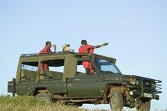Οι ανιχνεύσεις και ο τουρίστας Masai ψάχνουν τα ζώα από ένα Landcruiser κατά τη διάρκεια μιας κίνησης παιχνιδιών στη συντήρηση άγ Στοκ Φωτογραφίες