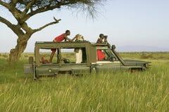 Οι ανιχνεύσεις και ο τουρίστας Masai ψάχνουν τα ζώα από ένα Landcruiser κατά τη διάρκεια μιας κίνησης παιχνιδιών στη συντήρηση άγ Στοκ Εικόνες
