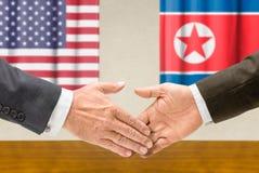 Οι αντιπρόσωποι των ΗΠΑ και της Βόρεια Κορέας τινάζουν τα χέρια στοκ εικόνα
