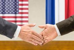 Οι αντιπρόσωποι των ΗΠΑ και της Γαλλίας τινάζουν τα χέρια στοκ εικόνες με δικαίωμα ελεύθερης χρήσης