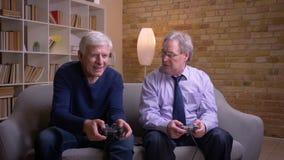 Οι ανώτεροι αρσενικοί φίλοι που παίζουν videogame μαζί με την κονσόλα πηδαλίων και παιχνιδιών χάνουν και παίρνουν απόθεμα βίντεο