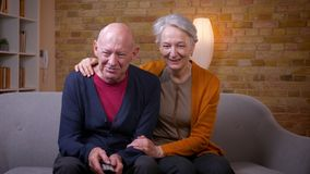 Οι ανώτεροι καυκάσιοι σύζυγοι προσέχουν την κωμωδία στη TV αγκαλιάζοντας ο ένας τον άλλον που είναι χαρούμενος και χαλαρωμένος στ φιλμ μικρού μήκους