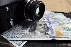 Οι αποδοχές στη φωτογραφία, μια κάμερα και δολάρια χρημάτων είναι στον πίνακα Στοκ φωτογραφία με δικαίωμα ελεύθερης χρήσης