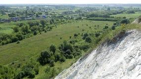 Οι απότομοι βράχοι των βουνών κιμωλίας προσφέρουν μια άποψη των σπιτιών κατωτέρω στοκ εικόνα