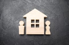 Οι αριθμοί ενός άνδρα και μιας γυναίκας στέκονται κοντά σε ένα ξύλινο σπίτι σε ένα συγκεκριμένο υπόβαθρο Σύζυγος και σύζυγος κοντ Στοκ Φωτογραφία