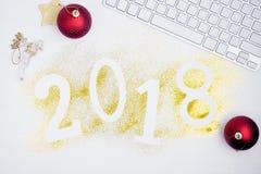 Οι αριθμοί το 2018 πυράκτωσης πολυτέλειας που γίνεται από χρυσό λαμπρό ακτινοβολούν στον άσπρο πίνακα με το πληκτρολόγιο και τη δ Στοκ Φωτογραφία