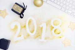 Οι αριθμοί το 2018 πυράκτωσης πολυτέλειας που γίνεται από χρυσό λαμπρό ακτινοβολούν στον άσπρο πίνακα με το πληκτρολόγιο και τη δ Στοκ Εικόνα