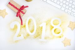Οι αριθμοί το 2018 πυράκτωσης πολυτέλειας που γίνεται από χρυσό λαμπρό ακτινοβολούν στον άσπρο πίνακα με το πληκτρολόγιο και τη δ Στοκ Εικόνες