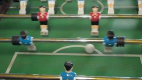 Οι αριθμοί των ποδοσφαιριστών κινούνται αριστερά και σωστοί άνθρωποι που παίζουν foosball plaers επιτραπέζιου ποδοσφαίρου Παιχνίδ φιλμ μικρού μήκους