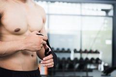οι αρσενικοί επίδεσμοι ένδυσης μαχητών στο μυϊκό άτομο πυγμών δεσμεύουν τον επίδεσμο επάνω Στοκ Εικόνα