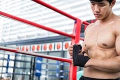 οι αρσενικοί επίδεσμοι ένδυσης μαχητών στο μυϊκό άτομο πυγμών δεσμεύουν τον επίδεσμο επάνω Στοκ φωτογραφία με δικαίωμα ελεύθερης χρήσης