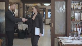 Οι αρσενικοί και θηλυκοί συνέταιροι συναντιούνται στο εστιατόριο Άνθρωποι που τινάζουν τα χέρια Κυρία σε ένα κομψό κοστούμι που έ απόθεμα βίντεο