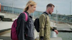 Οι αρσενικοί και θηλυκοί τουρίστες περπατούν με τις αποσκευές στην ηλιόλουστη οδό μετά από να φθάσουν απόθεμα βίντεο