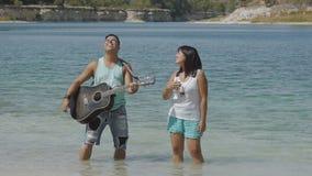 Οι αρσενικοί και θηλυκοί τραγουδιστές τραγουδούν ένα τραγούδι με μια κιθάρα απόθεμα βίντεο