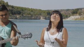 Οι αρσενικοί και θηλυκοί τραγουδιστές τραγουδούν ένα τραγούδι με μια κιθάρα φιλμ μικρού μήκους