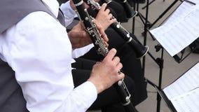 Οι αρσενικοί μουσικοί παίζουν τα κλαρινέτα στη δημοτική ορχήστρα αποδίδοντας εορταστικό σε υπαίθριο απόθεμα βίντεο