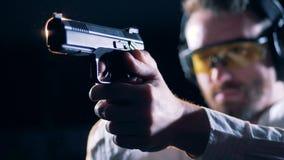 Οι αρσενικοί σκοπευτές κρατούν ένα πυροβόλο όπλο σε ένα δωμάτιο πυροβολισμού, κλείνουν επάνω απόθεμα βίντεο