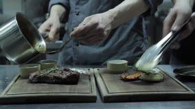 Οι αρχιμάγειρες προετοιμάζουν την μπριζόλα και τα ψημένα στη σχάρα λαχανικά για τους επισκέπτες του εστιατορίου απόθεμα βίντεο