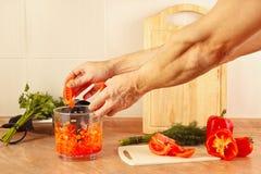 Οι αρχιμάγειρες χεριών βάζουν την τεμαχισμένη ντομάτα στο μπλέντερ Στοκ Εικόνες