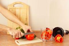 Οι αρχιμάγειρες χεριών κόβουν την κόκκινη ντομάτα στον πίνακα κουζινών Στοκ εικόνες με δικαίωμα ελεύθερης χρήσης