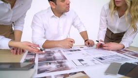 Οι αρχιτέκτονες, οι οικοδόμοι, ή οι νέοι σχεδιαστών επάνω από το σαλόνι επιλέγουν το χρώμα για το εσωτερικό δημιουργικός φιλμ μικρού μήκους