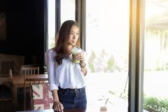 Οι ασιατικές γυναίκες πίνουν τον καφέ και κοιτάζουν έξω Στοκ Φωτογραφία
