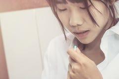 Οι ασιατικές γυναίκες παίρνουν μια ιατρική στο κρεβάτι στοκ φωτογραφία