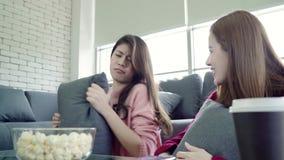 Οι ασιατικές γυναίκες που παίζουν την πάλη μαξιλαριών και που τρώνε popcorn στο καθιστικό στο σπίτι, ομάδα φίλου συγκατοίκων απολ απόθεμα βίντεο