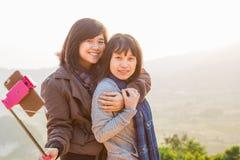 Οι ασιατικές γυναίκες τουριστών παίρνουν τη φωτογραφία μαζί ενώ οδοιπορία βουνών στοκ εικόνες