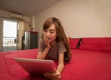 Οι ασιατικές γυναίκες χρησιμοποιούν την ταμπλέτα στο κρεβάτι το πρωί Ασιατική γυναίκα στο κρεβάτι που ελέγχει τα κοινωνικά apps στοκ εικόνα