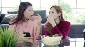 Οι ασιατικές γυναίκες χρησιμοποιώντας το smartphone και τρώγοντας popcorn στο καθιστικό στο σπίτι, ομάδα φίλου συγκατοίκων απολαμ απόθεμα βίντεο