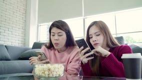 Οι ασιατικές γυναίκες χρησιμοποιώντας το smartphone και τρώγοντας popcorn στο καθιστικό στο σπίτι, ομάδα φίλου συγκατοίκων απολαμ φιλμ μικρού μήκους